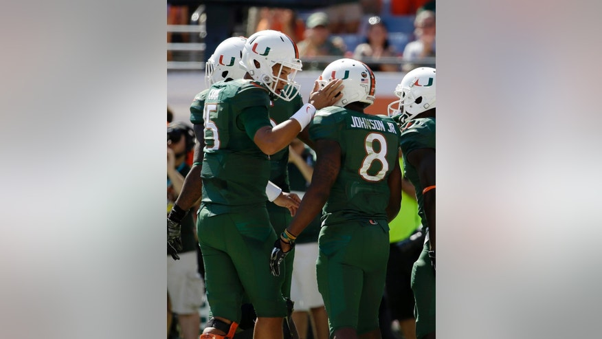 Miami quarterback Brad Kaaya (15) congratulates running back Duke Johnson (8) after Johnson scored a touchdown during the first half of an NCAA football game against North Carolina, Saturday, Nov. 1, 2014, in Miami Gardens, Fla. (AP Photo/Lynne Sladky)