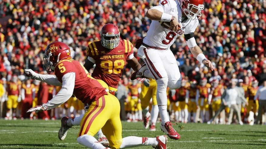 Oklahoma quarterback Trevor Knight runs past Iowa State defensive back Kamari Cotton-Moya, left, and defensive end Trent Taylor (98) during an 8-yard touchdown run in the first half of an NCAA college football game, Saturday, Nov. 1, 2014, in Ames, Iowa. (AP Photo/Charlie Neibergall)