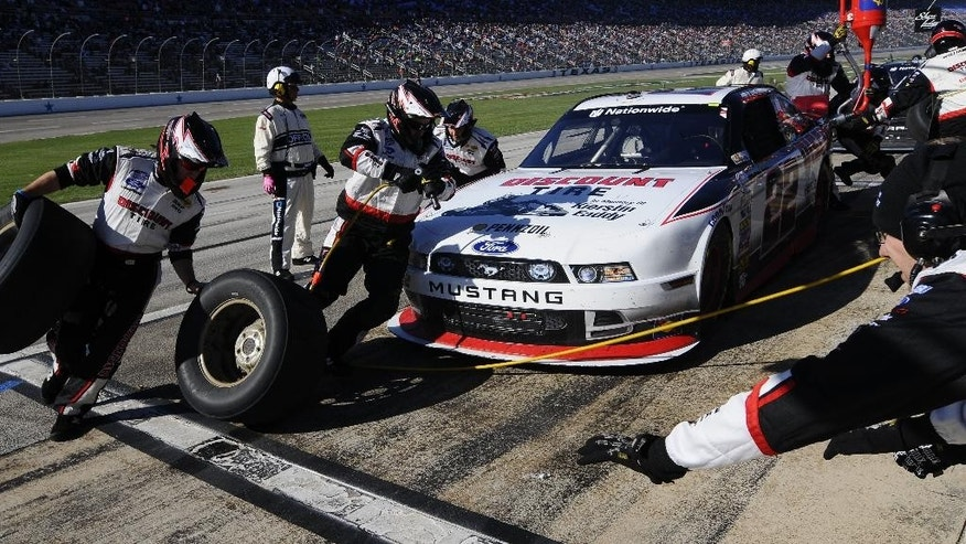 Nationwide Series driver Joey Logano (22) takes on new tires during a pits stop during the NASCAR Nationwide Series auto race at Texas Motor Speedway in Fort Worth, Texas, Saturday, Nov. 1, 2014. (AP Photo/Ralph Lauer)