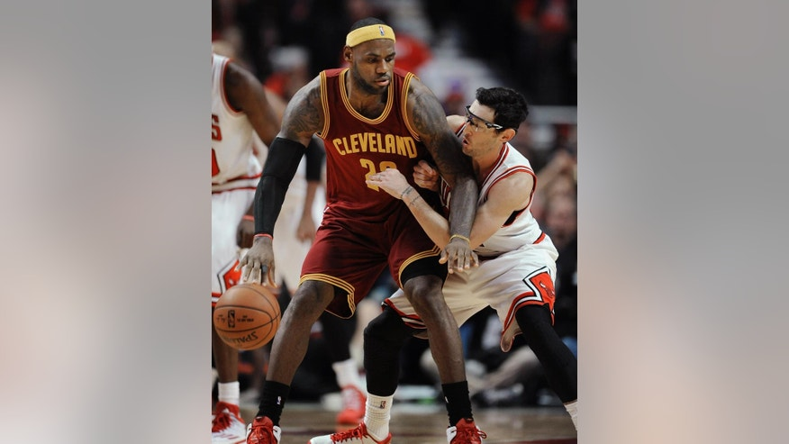 Cleveland Cavaliers' LeBron James (23) works with the ball against Chicago Bulls' Kirk Hinrich during overtime of an NBA basketball game in Chicago, Friday, Oct. 31, 2014. Cleveland won 114-108. (AP Photo/Paul Beaty)