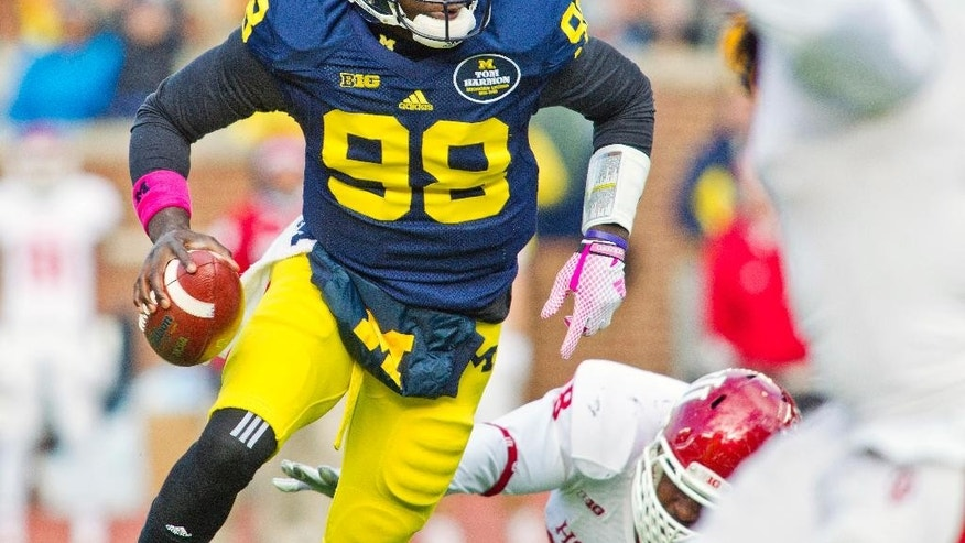 Michigan quarterback Devin Gardner (98) scrambles away from Indiana defenders with the ball in the first quarter of an NCAA college football game in Ann Arbor, Mich., Saturday, Nov. 1, 2014. (AP Photo/Tony Ding)