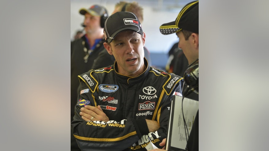Driver Matt Kenseth speaks with a crew member in the garage during practice for Sunday's NASCAR Sprint Cup series auto race at the Texas Motor Speedway in Fort Worth, Texas, Saturday, Nov. 1, 2014. (AP Photo/Randy Holt)