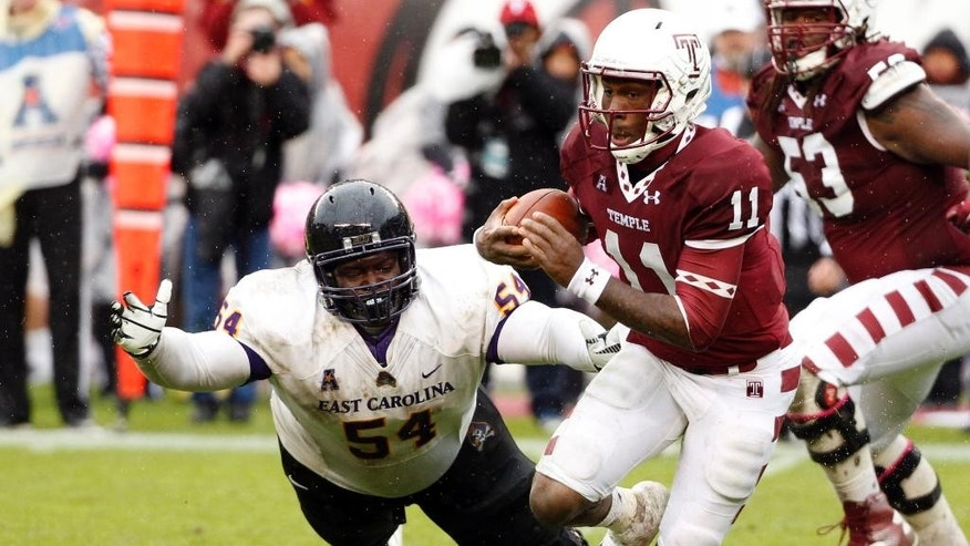 Temple quarterback P.J. Walker, right, scrambles with the ball as he gets past the diving East Carolina nose tackle Terry Williams, left, during the second half an NCAA college football game, Saturday, Nov. 1, 2014, in Philadelphia. Temple won 20-10. (AP Photo/Chris Szagola)