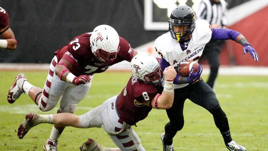East Carolina wide receiver Quay Johnson, right, runs with the ball after the catch as Temple linebacker Tyler Matakevich, center, and defensive lineman Averee Robinson, left, try to bring him down during the second half an NCAA college football game, Saturday, Nov. 1, 2014, in Philadelphia. Temple won 20-10. (AP Photo/Chris Szagola)