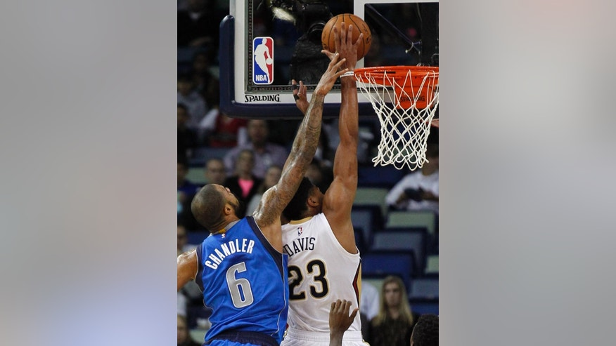 Dallas Mavericks center Tyson Chandler (6) blocks the shot of New Orleans Pelicans forward Anthony Davis (23) in the first half of an NBA basketball game in New Orleans, Saturday, Nov. 1, 2014. (AP Photo/Bill Haber)