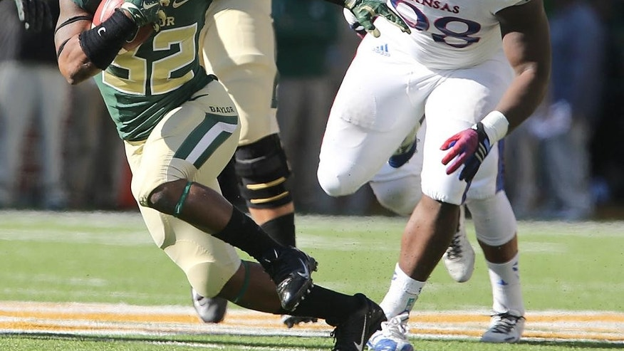 Baylor running back Shock Linwood (32) runs past Kansas linebacker Courtney Arnick (28) in the first half of an NCAA college football game, Saturday, Nov. 1, 2014, in Waco, Texas. (AP Photo/ Jerry Larson)