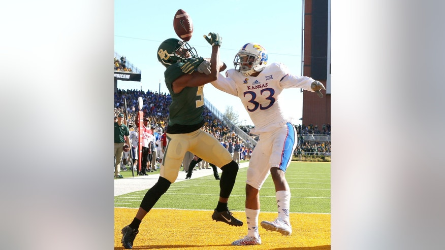 Kansas safety Cassius Sendish (33) breaks up the pass intended for Baylor wide receiver KD Cannon in the first half of an NCAA college football game, Saturday, Nov. 1, 2014, in Waco, Texas. (AP Photo/ Jerry Larson)