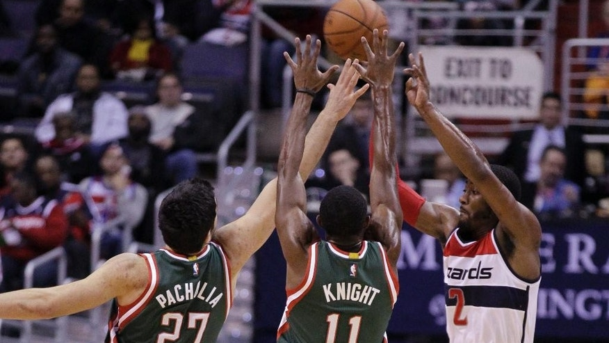 Washington Wizards' John Wall (2) passes the ball as Milwaukee Bucks' Zaza Pachulia (27) and Brandon Knight (11) defend during the first half of an NBA basketball game, Saturday, Nov. 1, 2014, in Washington. (AP Photo/Luis M. Alvarez)