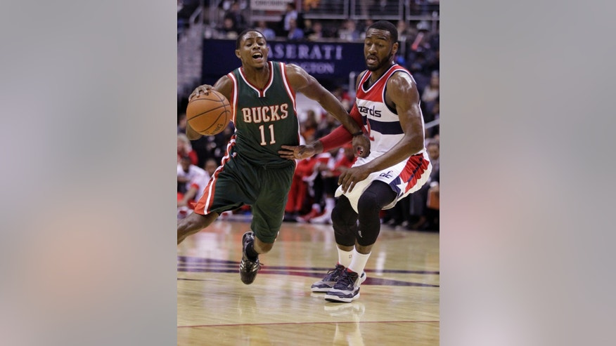 Washington Wizards' John Wall (2) fouls Milwaukee Bucks' Brandon Knight (11) during the first half of an NBA basketball game, Saturday, Nov. 1, 2014, in Washington. (AP Photo/Luis M. Alvarez)