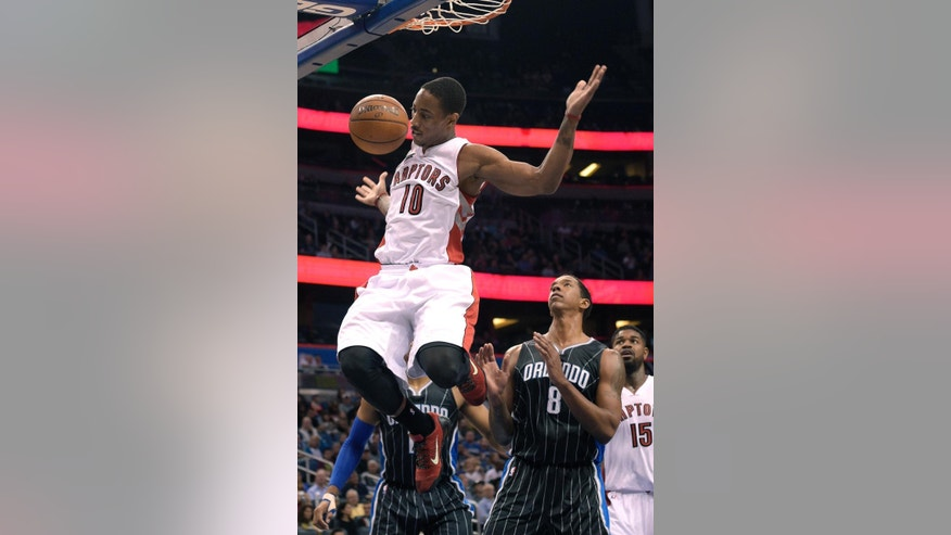 Toronto Raptors guard DeMar DeRozan (10) hangs in the air after dunking the ball in front of Orlando Magic forward Channing Frye (8) during the first half of an NBA basketball game in Orlando, Fla., Saturday, Nov. 1, 2014. (AP Photo/Phelan M. Ebenhack)