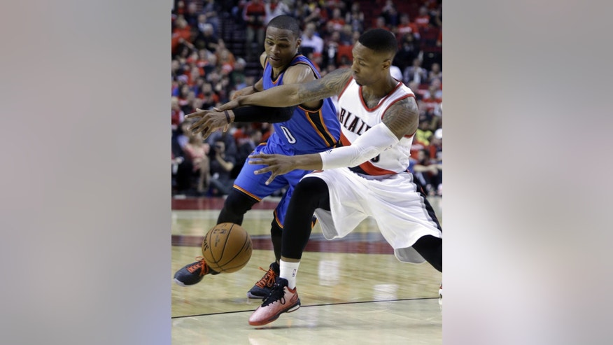 Oklahoma City Thunder guard Russell Westbrook, left, battles for the ball with Portland Trail Blazers guard Damian Lillard during the second half of an NBA basketball game in Portland, Ore., Wednesday, Oct. 29, 2014.  Westbrook score 38 points as the Trail Blazers won 106-89.(AP Photo/Don Ryan)