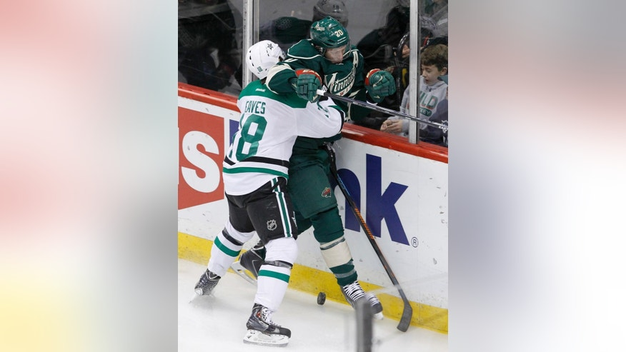 Dallas Stars right wing Patrick Eaves (18) checks Minnesota Wild defenseman Ryan Suter (20) off the puck and into the boards during the first period of an NHL hockey game in St. Paul, Minn., Saturday, Nov. 1, 2014. (AP Photo/Ann Heisenfelt)