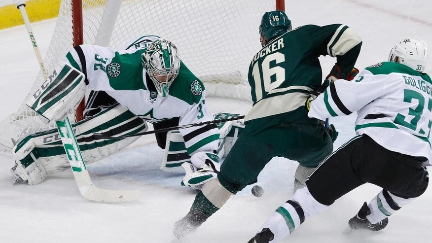 Dallas Stars goalie Kari Lehtonen (32), of Finland, deflects a shot by Minnesota Wild left wing Jason Zucker (16) in front of Stars defenseman Alex Goligoski (33) during the first period of an NHL hockey game in St. Paul, Minn., Saturday, Nov. 1, 2014. (AP Photo/Ann Heisenfelt)