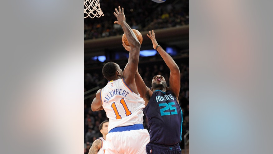 Charlotte Hornets center Al Jefferson (25) attempts a shot as New York Knicks center Samuel Dalembert attempts to block the shot during the first half of an NBA basketball game Sunday, Nov. 2, 2014, in New York. (AP Photo/Bill Kostroun)