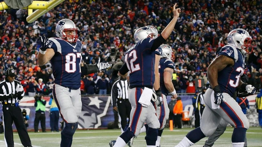 New England Patriots tight end Rob Gronkowski, left, reacts after catching a touchdown pass from quarterback Tom Brady, celebrating at center, in the second half of an NFL football game against the Denver Broncos on Sunday, Nov. 2, 2014, in Foxborough, Mass. (AP Photo/Elise Amendola)