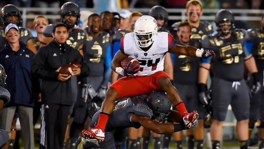 Arizona running back Terris Jones-Grigsby (24) jumps over UCLA defensive back Fabian Moreau (10) for a first down during the first half of an NCAA college football game, Saturday, Nov. 1, 2014, in Pasadena, Calif. (AP Photo/Gus Ruelas)