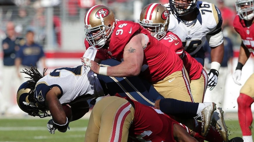 St. Louis Rams running back Tre Mason, left, is tackled by San Francisco 49ers defensive tackle Justin Smith (94) and safety Eric Reid, bottom, during the second quarter of an NFL football game in Santa Clara, Calif., Sunday, Nov. 2, 2014. (AP Photo/Marcio Jose Sanchez)