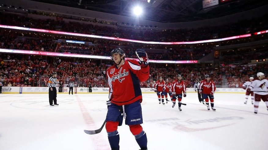 Washington Capitals left wing Alex Ovechkin, from Russia, comes to the bench to celebrate his goal in the first period of an NHL hockey game against the Arizona Coyotes, Sunday, Nov. 2, 2014, in Washington. (AP Photo/Alex Brandon)