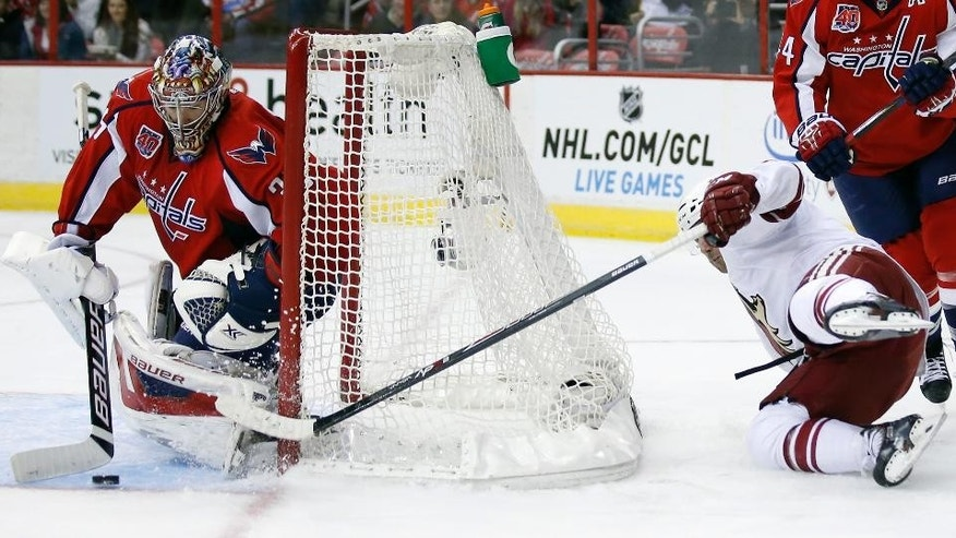 Arizona Coyotes center Sam Gagner (9) reaches around to shoot the puck and his shot is blocked by Washington Capitals goalie Justin Peters (35) in the second period of an NHL hockey game, Sunday, Nov. 2, 2014, in Washington. (AP Photo/Alex Brandon)