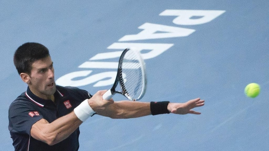 Serbia's Novak Djokovic returns the ball to Milos Raonic of the Canada during their final match at the ATP World Tour Masters tennis tournament at Bercy stadium in Paris, France,  Sunday, Nov. 2, 2014. (AP Photo/Jacques Brinon)