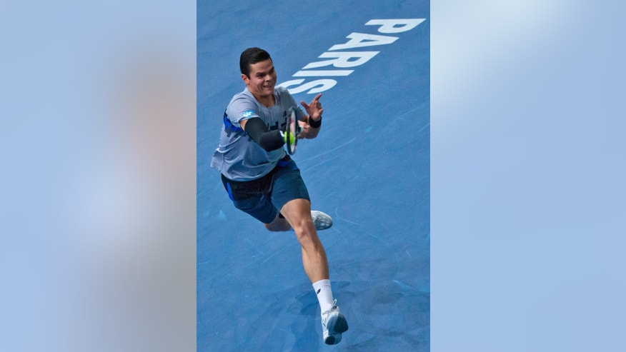 Milos Raonic of the Canada returns the ball to Serbia's Novak Djokovic during their final match at the ATP World Tour Masters tennis tournament at Bercy stadium in Paris,  Sunday, Nov. 2, 2014. (AP Photo/Jacques Brinon)