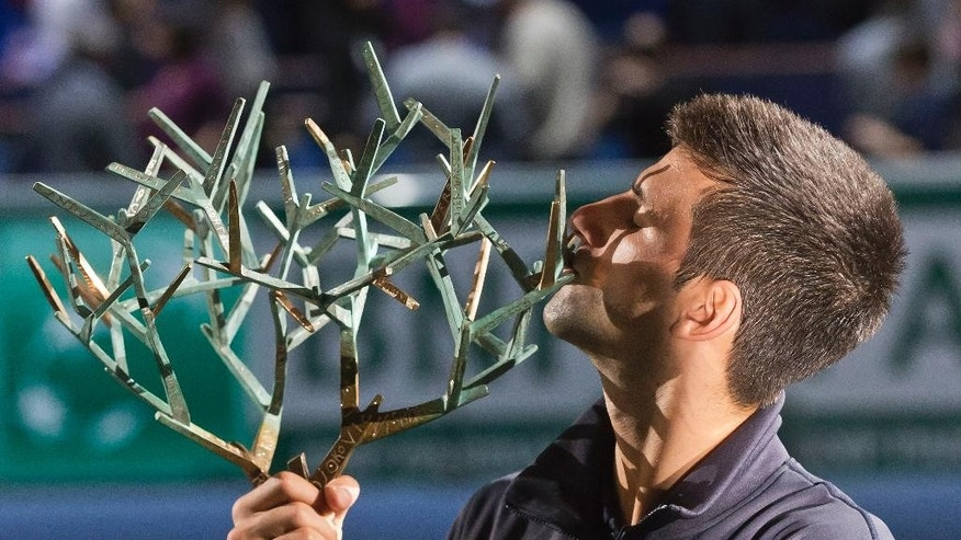Novak Djokovic of Serbia, holds the trophy as he kissed it after he defeated Milos Raonic of Canada during their final match at the ATP World Tour Masters tennis tournament at Bercy stadium in Paris, France, Sunday, Nov. 2, 2014. Djokovic won 6-2, 6-3. (AP Photo/Michel Euler)