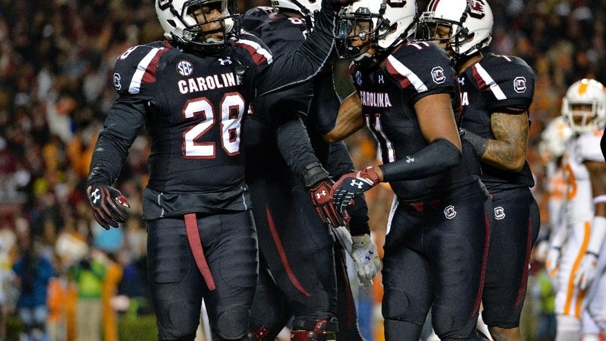 South Carolina's Mike Davis (28) congratulates Pharoh Cooper after Cooper scored a touchdown during the first half of an NCAA college football game against Tennessee in Columbia, S.C., Saturday, Nov. 1, 2014. (AP Photo/ Richard Shiro)