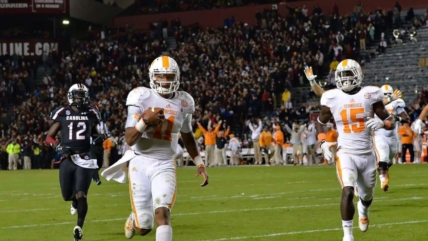 Tennesse quarterback Joshua Dobbs, front left, runs into the end zone for a touchdown during the first half of an NCAA college football game against South Carolina in Columbia, S.C., Saturday, Nov. 1, 2014. (AP Photo/ Richard Shiro)
