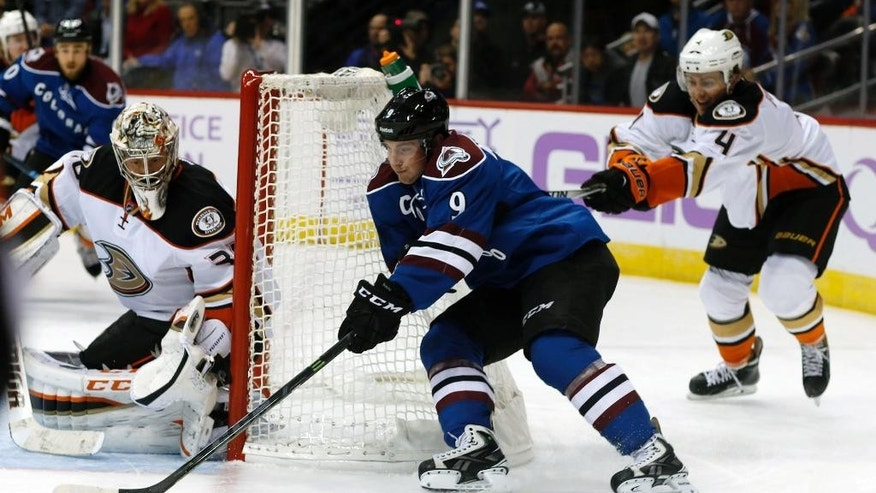 Colorado Avalanche center Matt Duchene, center, wraps around the net to shoot on Anaheim Ducks goalie Jason LaBarbera, left, as defenseman Cam Fowler covers in the first period of an NHL hockey game in Denver on Sunday, Nov. 2, 2014. (AP Photo/David Zalubowski)