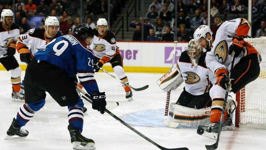 Colorado Avalanche center Nathan MacKinnon, left, has his shot blocked by Anaheim Ducks center Ryan Kesler, right, as goalie Jason LaBarbera covers the net in the first period of an NHL hockey game in Denver on Sunday, Nov. 2, 2014. (AP Photo/David Zalubowski)