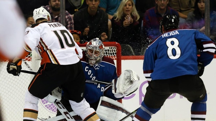 Anaheim Ducks right wing Corey Perry, left, scores past Colorado Avalanche goalie Semyon Varlamov, center, of Russia, as defenseman Jan Hejda, of the Czech Republic, looks on in the first period of an NHL hockey game in Denver on Sunday, Nov. 2, 2014. (AP Photo/David Zalubowski)