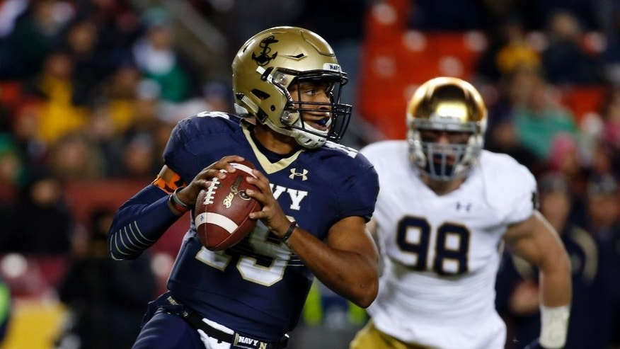 Navy quarterback Keenan Reynolds (19) looks to pass as he is pursued by Notre Dame defensive lineman Andrew Trumbetti (98) during the first half an NCAA college football game Saturday, Nov. 1, 2014, in Landover, Md. (AP Photo/Alex Brandon)