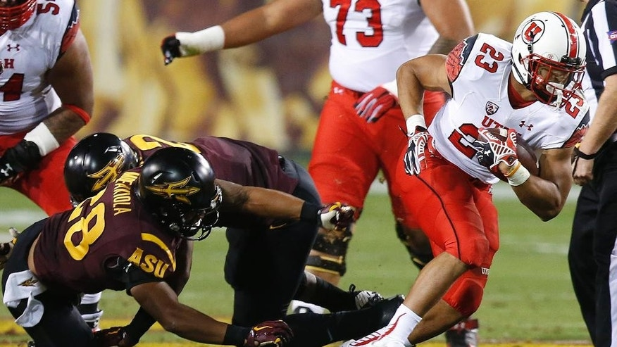 Utah's Devontae Booker (23) runs past Arizona State's Viliami Moeakiola (28) in the first half of an NCAA college football game on Saturday, Nov. 1, 2014, in Tempe, Ariz. (Photo/Ross D. Franklin)