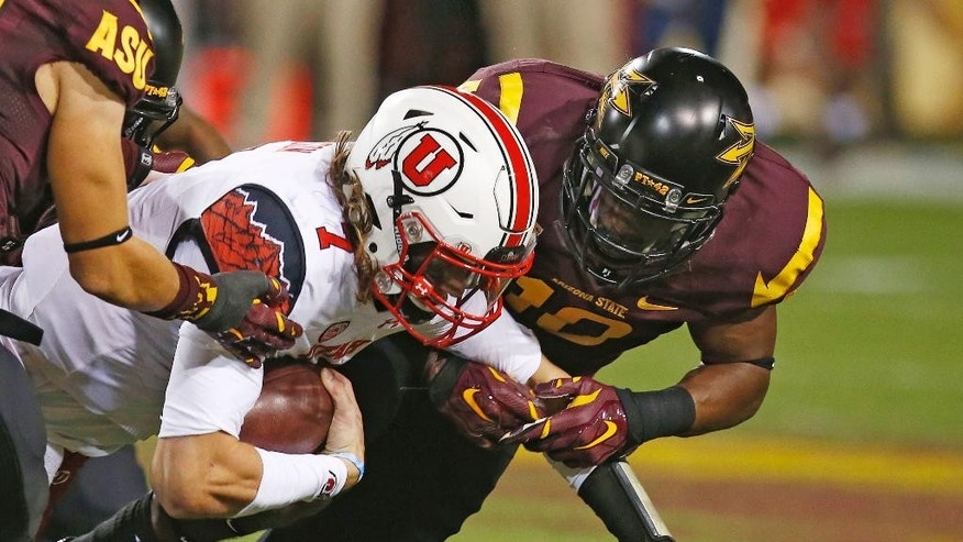 Utah's Travis Wilson (7) gets tackled by Arizona State's Kweishi Brown, right, in the first half of an NCAA college football game on Saturday, Nov. 1, 2014, in Tempe, Ariz. (Photo/Ross D. Franklin)
