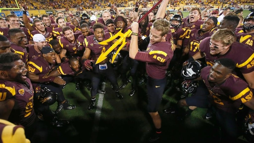 Arizona State's Zane Gonzalez gets ready to send a pitchfork into the ground as his teammates cheer him on, after his kicked a game-winning field goal against Utah, after an NCAA college football game on Saturday, Nov. 1, 2014, in Tempe, Ariz.  Arizona State defeated the Utah 19-16 in overtime. (AP Photo/Ross D. Franklin)