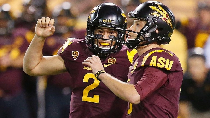Arizona State's Zane Gonzalez, right, celebrates his game-winning field goal against Utah with teammate Mike Bercovici (2) in overtime of an NCAA college football game on Saturday, Nov. 1, 2014, in Tempe, Ariz.  Arizona State defeated the Utah 19-16 in overtime. (Photo/Ross D. Franklin)