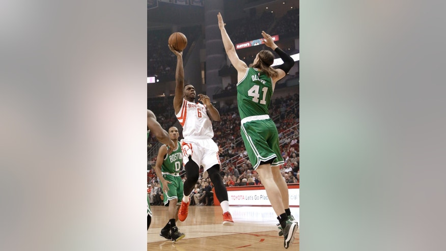 Houston Rockets' Terrence Jones (6) shoots between Boston Celtics defenders Kelly Olynyk (41) and Avery Bradley (0) during the first half of an NBA basketball game Saturday, Nov. 1, 2014, in Houston. (AP Photo/Pat Sullivan)