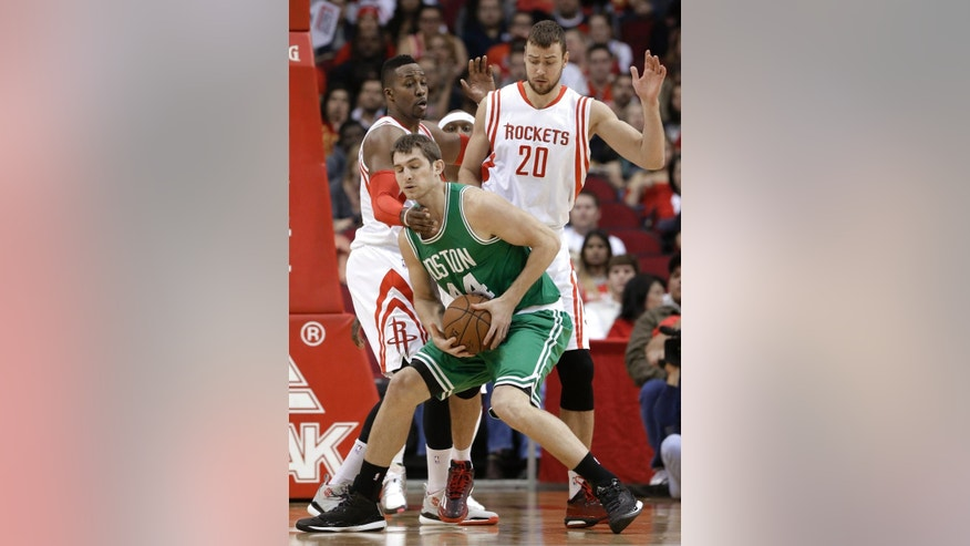 Boston Celtics' Tyler Zeller (44) is pressured by Houston Rockets' Donatas Motiejunas (20) and Dwight Howard during the first half of an NBA basketball game Saturday, Nov. 1, 2014, in Houston. (AP Photo/Pat Sullivan)