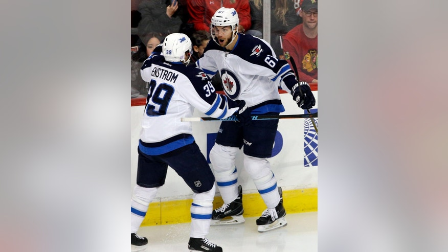 Winnipeg Jets right wing Michael Frolik (67) celebrates with defenseman Toby Enstrom (39) after scoring his goal during the first period of an NHL hockey game against the Chicago Blackhawks in Chicago, Sunday, Nov. 2, 2014. (AP Photo/Nam Y. Huh)