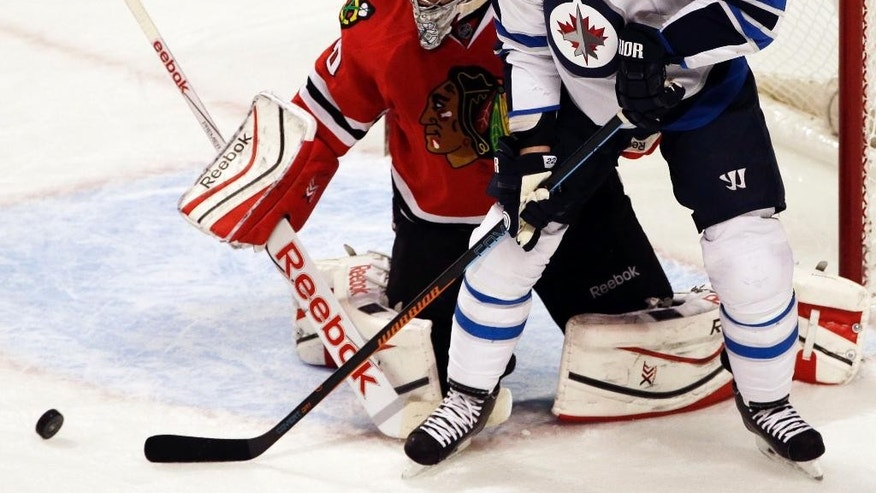 Winnipeg Jets right wing Chris Thorburn (22) and Chicago Blackhawks goalie Corey Crawford watch the puck during the first period of an NHL hockey game in Chicago, Sunday, Nov. 2, 2014. (AP Photo/Nam Y. Huh)