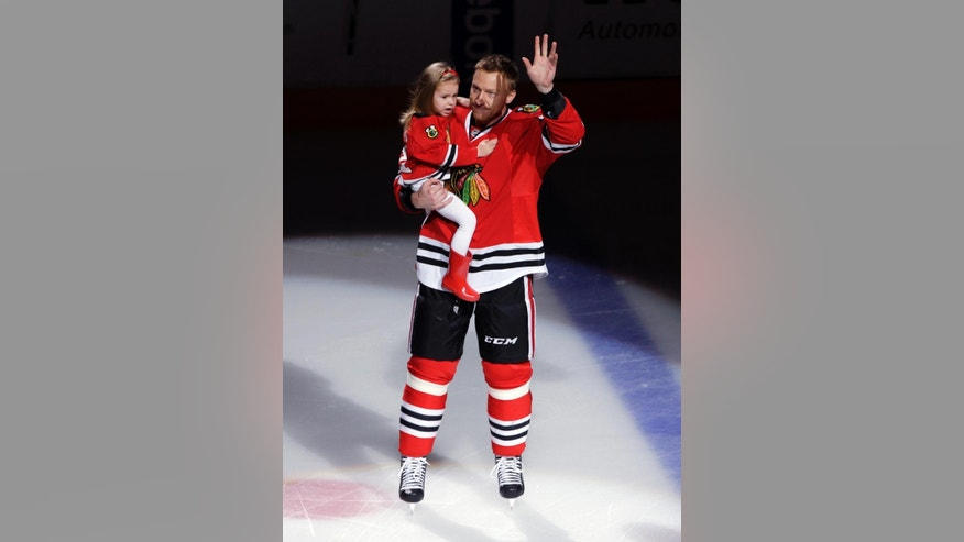 Chicago Blackhawks right wing Marian Hossa holds his daughter Mia Hossova as he celebrates his 1000-point milestone before an NHL hockey game against the Winnipeg Jets in Chicago, Sunday, Nov. 2, 2014. (AP Photo/Nam Y. Huh)