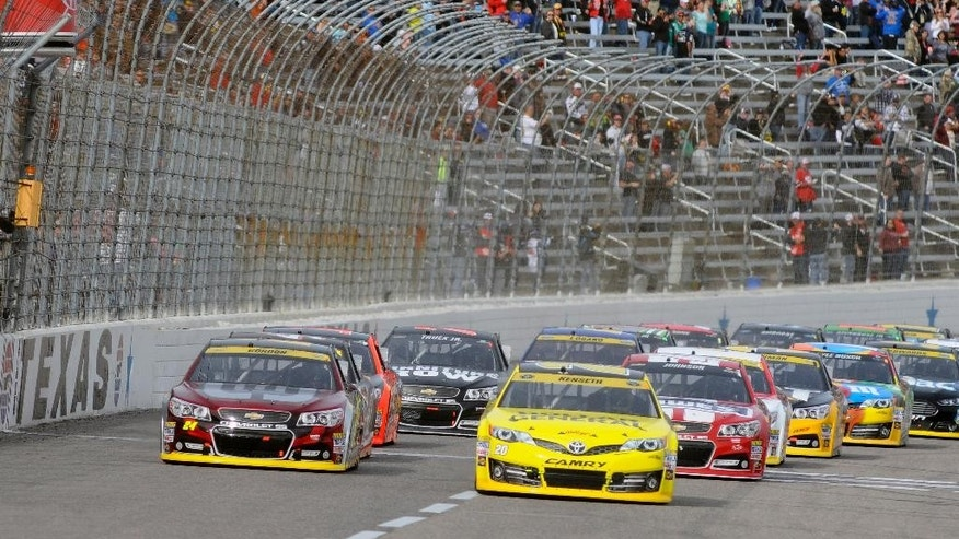 The green flags drops on Matt Kenseth (20), Jeff Gordon (24) and the rest of the field of drivers starting the NASCAR Sprint Cup Series auto race at Texas Motor Speedway in Fort Worth, Texas, Sunday, Nov. 2, 2014. (AP Photo/Ralph Lauer)