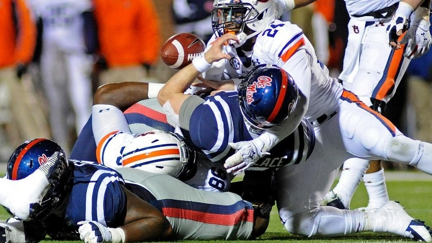 Mississippi quarterback Bo Wallace (14) fumbles the ball while being tackled by Auburn defensive lineman DaVonte Lambert (86) and defensive back Derrick Moncrief (24) during the second half of an NCAA college football game in Oxford, Miss., Saturday, Nov. 1, 2014. Auburn recovered the fumble. Auburn won 35-31. (AP Photo/The Daily Mississippian, Thomas Graning)