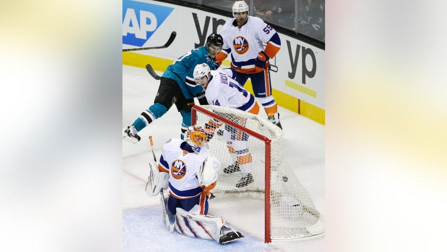 New York Islanders goalie Jaroslav Halak, bottom, of Slovakia, is beaten for a goal on a shot from San Jose Sharks' Tomas Hertl, not pictured, during the first period of an NHL hockey game Saturday, Nov. 1, 2014, in San Jose, Calif. (AP Photo/Marcio Jose Sanchez)