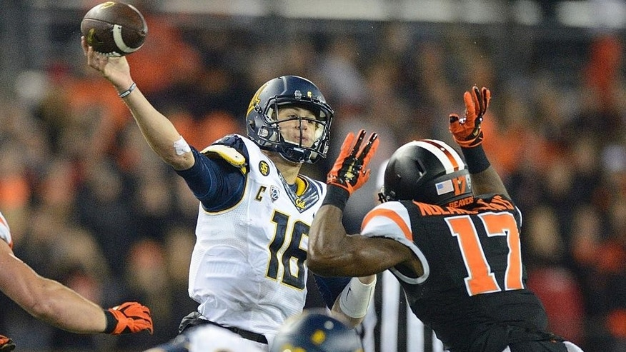 California quarterback Jared Goff (16) passes as he get defensive pressure from Cyril Noland-Lewis (17) of Oregon State during an NCAA college football game in Corvallis, Ore., Saturday, Nov. 1, 2014. (AP Photo/Troy Wayrynen)