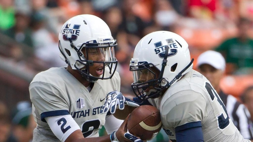 Utah State quarterback Kent Myers (2) hands off the football to running back Joe Hill (32) during the first quarter of an NCAA college football game, Saturday, Nov. 1, 2014, in Honolulu. (AP Photo/Eugene Tanner)