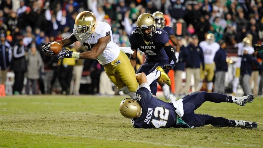 Notre Dame running back Tarean Folston (25) leaps for the end zone for a touchdown against Navy safety George Jamison (42) during the second half of an NCAA college football game, Saturday, Nov. 1, 2014, in Landover, Md. Notre Dame won 49-39. (AP Photo/Nick Wass)