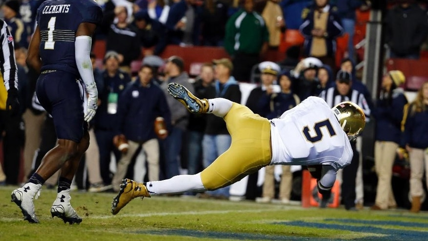 Notre Dame quarterback Everett Golson (5) dives for a touchdown past Navy cornerback Brendon Clements (1) during the second half an NCAA college football game, Saturday, Nov. 1, 2014, in Landover, Md. Notre Dame won 49-39. (AP Photo/Alex Brandon)