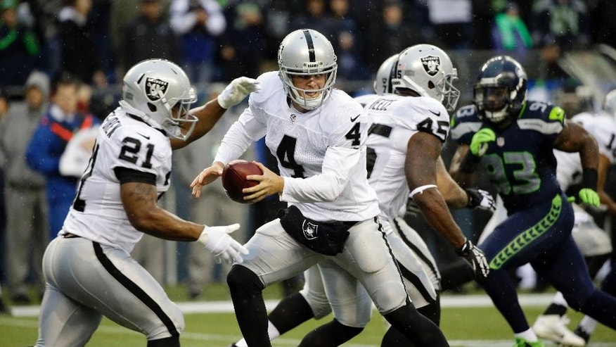 Oakland Raiders quarterback Derek Carr (4) hands off to running back Maurice Jones-Drew (21) in the second half of an NFL football game against the Seattle Seahawks, Sunday, Nov. 2, 2014, in Seattle. (AP Photo/Elaine Thompson)