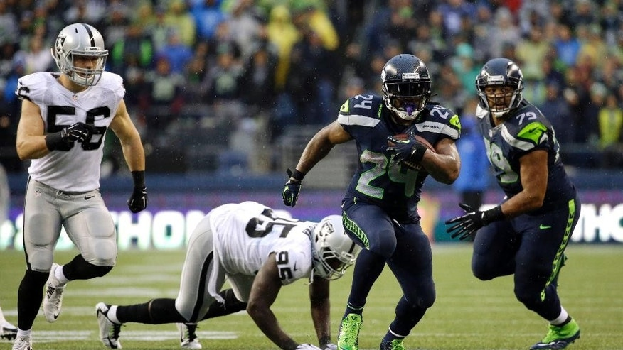 Seattle Seahawks running back Marshawn Lynch (24) runs after avoiding a tackle by Oakland Raiders defensive end Benson Mayowa (95) in the second half of an NFL football game, Sunday, Nov. 2, 2014, in Seattle. (AP Photo/Elaine Thompson)